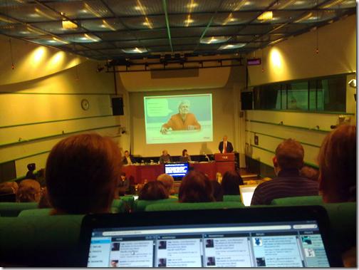 Kuva seminaarista auditorion takariviltä. Adagen puheenvuoro menossa ja valkokankaalla kuva nettiä käyttävästä seniorikansalaisesta.